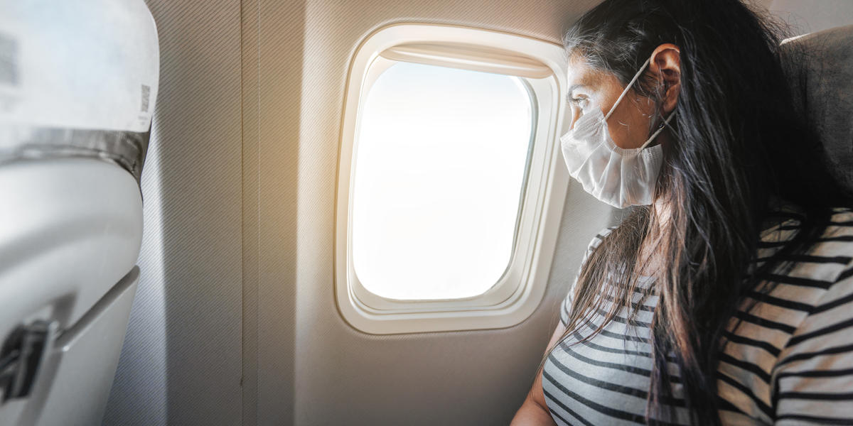 Traveler in mask looking out airplane window